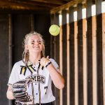 Courtney throws a softball in the air in the dugout