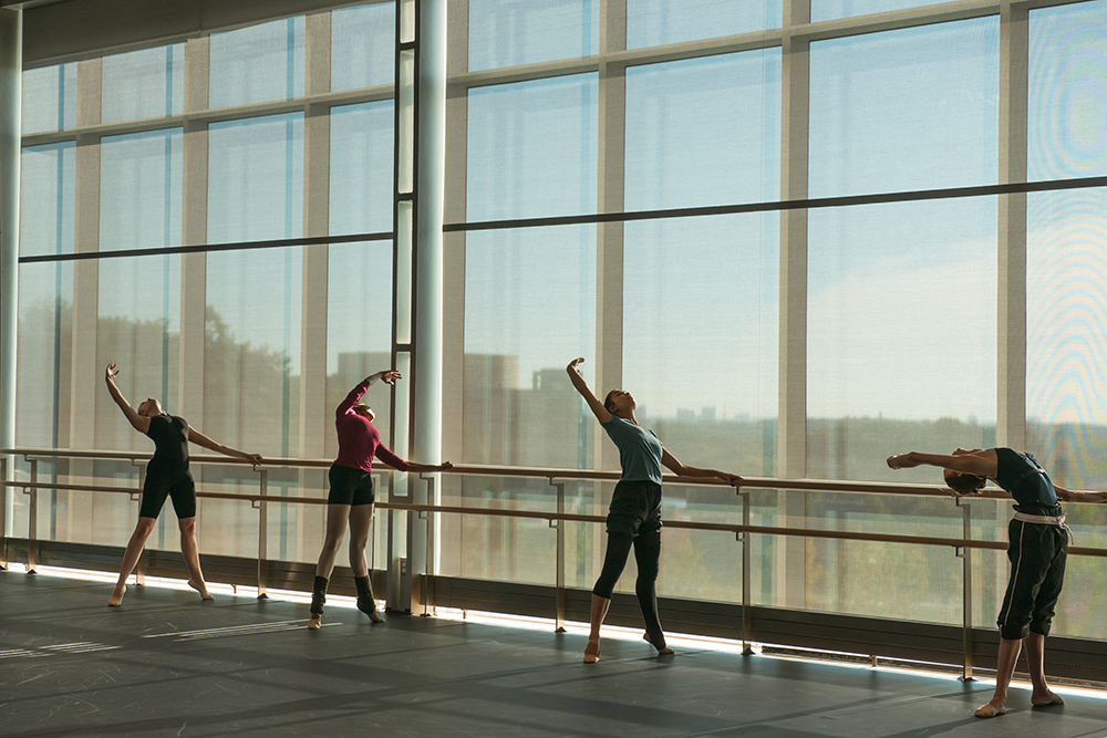 Four students at the barre in the UMBC dance cube
